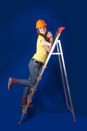Girl in hard hat with paint rollers on stepladder