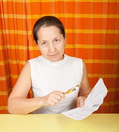 lamentable: mature woman looking at utility bills through  magnifier