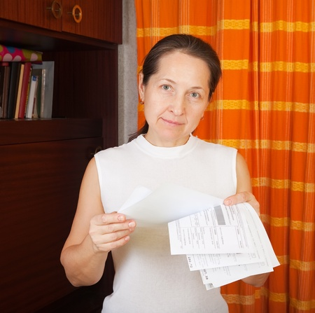 utility payments: Sad mature woman with utility bills  at her home