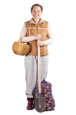 Happy pastoral  woman  with spade and harvested potatoes over white photo