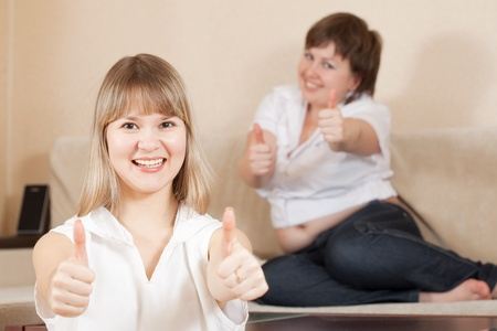 Happy young women showing thumb up sign in home photo