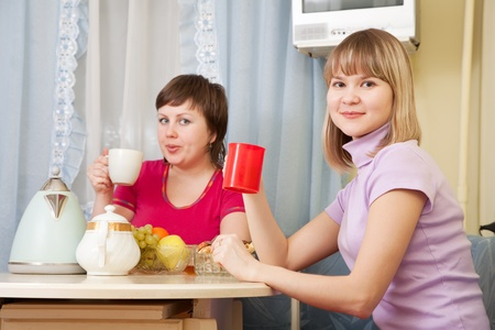 Two smiling women have tea in kitchen Stock Photo - 9338839