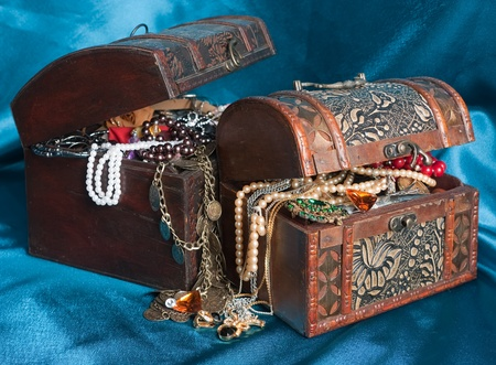 Two wooden treasure chests with valuables on blue textile photo