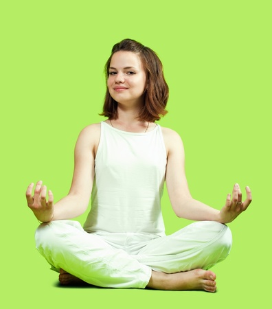 Young girl doing yoga over green background photo