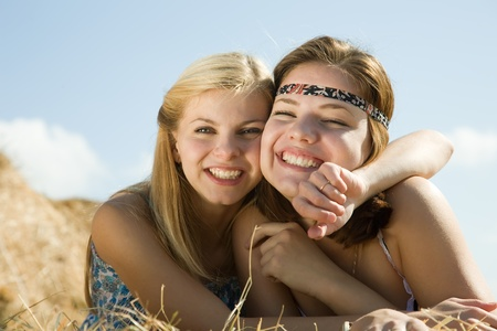 Happy girls on fresh hay at field Stock Photo - 9359847