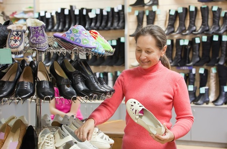Mature woman chooses shoes at shoes shop Stock Photo - 9395973
