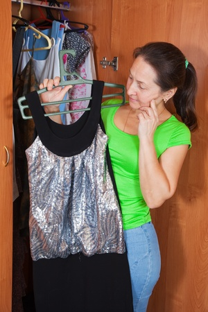 Mature woman standing at wardrobe.  photo