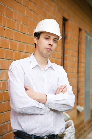 tasker: portrait of  man in hardhat  against  the brick wall