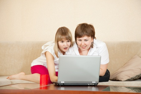 wonder women sitting on sofa in living room with laptop Stock Photo - 9413740