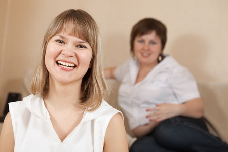 Two happy casual girls in home interior photo
