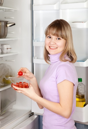Young woman taking  Cherry-tomatoes    from refrigerator  at home photo