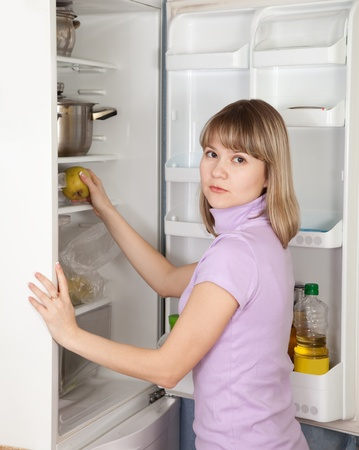 Young woman taking green apple  from refrigerator  at home photo