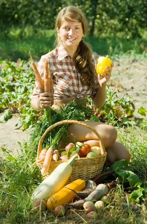 Cheerful girl sitting near basket of harvested vegetables and fruits photo