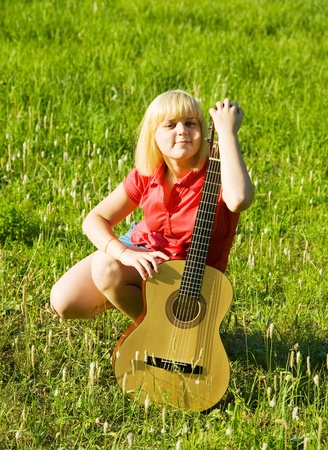 Blonde girl with guitar against green grass photo