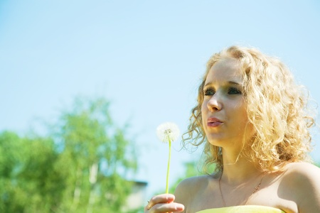 Young girl blowing seeds of dandelion flower Stock Photo - 9440027