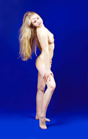 nude woman standing: Standing long-haired blonde nudity girl on blue background
