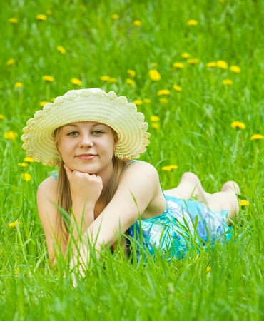 barefoot teen girl in hat is lying at meadow photo
