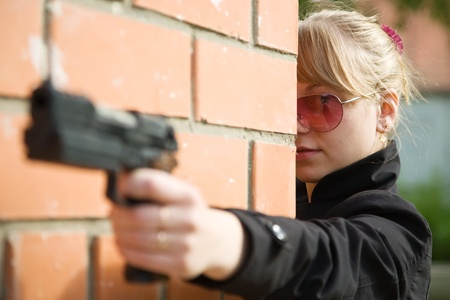 airsoft: woman with gun against  the brick wall