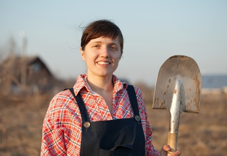 Happy female farmer  with spade  in country photo