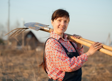 horizont: Happy female farmer  with spade and pitchfork in rural