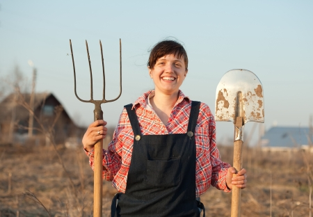Happy female farmer  with spade and hayfork in field photo