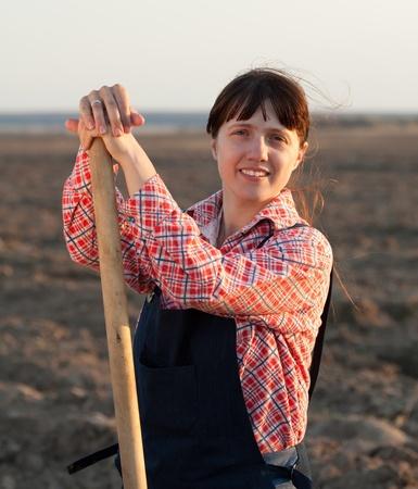 Female farmer  with spade in plowed field photo