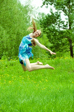 Jumping long-haired teen girl against nature photo