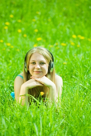 young girl listen to the music with head phones outdoor photo