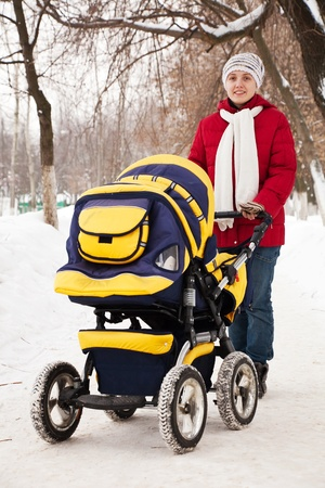 Young woman with pram walking at winter park photo
