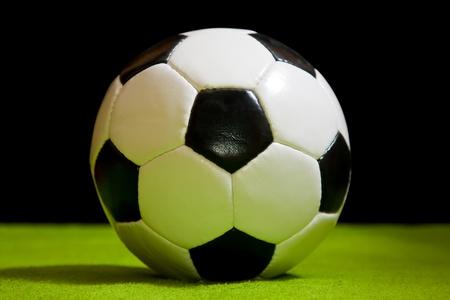 futbol: pallone da calcio classico sul verde sopra nero