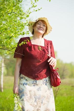 portrait of senior woman against spring  landscape photo