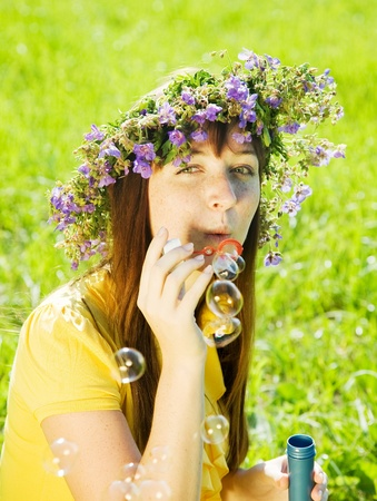 girl making soap bubbles on meadow grass photo