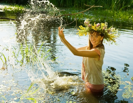 wet clothes: girl  in russian traditional clothes playing into water Stock Photo