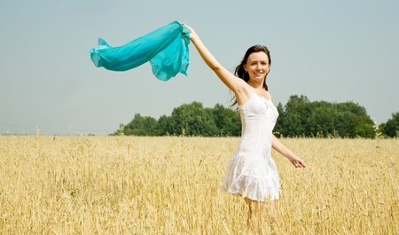 Happy young woman in white dress at field photo