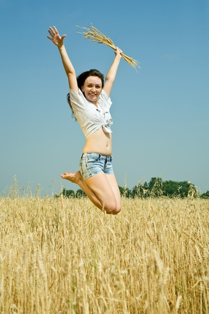 Jumping girl  with  wheat ear at  field in summer photo
