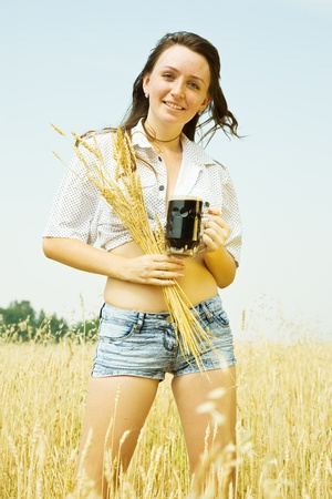 Girl  with quass and wheat ear  at wheat field photo