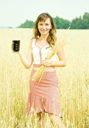 Girl  with beer and wheat ears  at cereals field photo