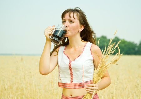 Girl  with kvass at cereals field in summer Stock Photo - 9546835