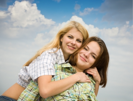 Two girls together against cloudy sky Stock Photo - 9547013