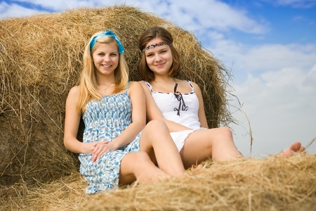 Farm girls resting on fresh hay bale photo