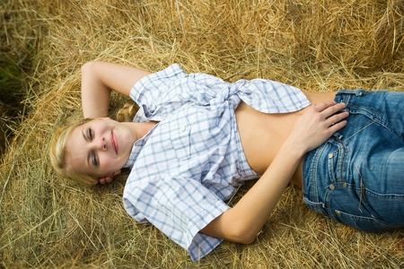 Pretty girl in checked shirt resting on hay  photo