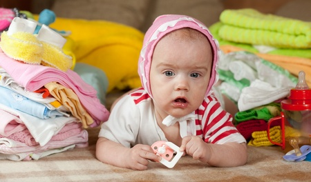 Baby girl with heap of baby's wear laying on checked blanket Stock Photo - 9547572