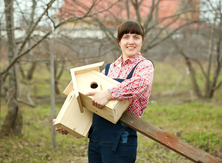 Woman with two new birdhouses at garden photo