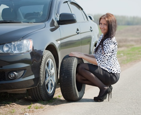 summer tire: woman during the wheel changing at road