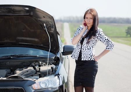 broken car: mujer de mediana edad espera apoyo cerca de su coche rota Foto de archivo