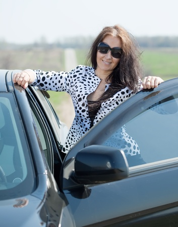 capping: middle age woman with her car at road Stock Photo