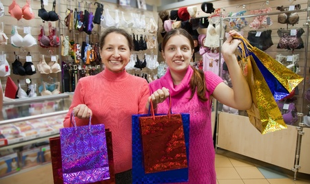 Two happy women with shopping bags against  counter in underwear shop Stock Photo - 9577699
