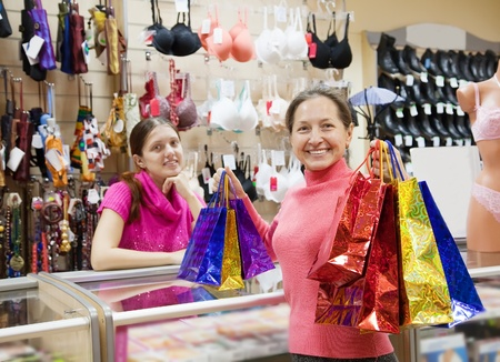 Buyer  and salesman  with purchases at  counter in   shop. Focus on buyer photo