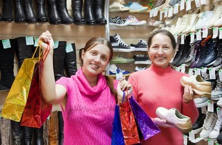 comprando zapatos: Dos mujeres felices con bolsas en zapatos de moda almacenar Foto de archivo