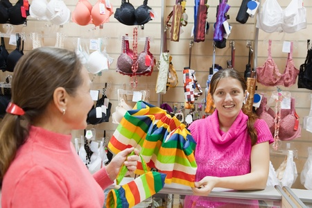 Saleswoman and buyer at  counter in underwear shop. Focus on salesman photo